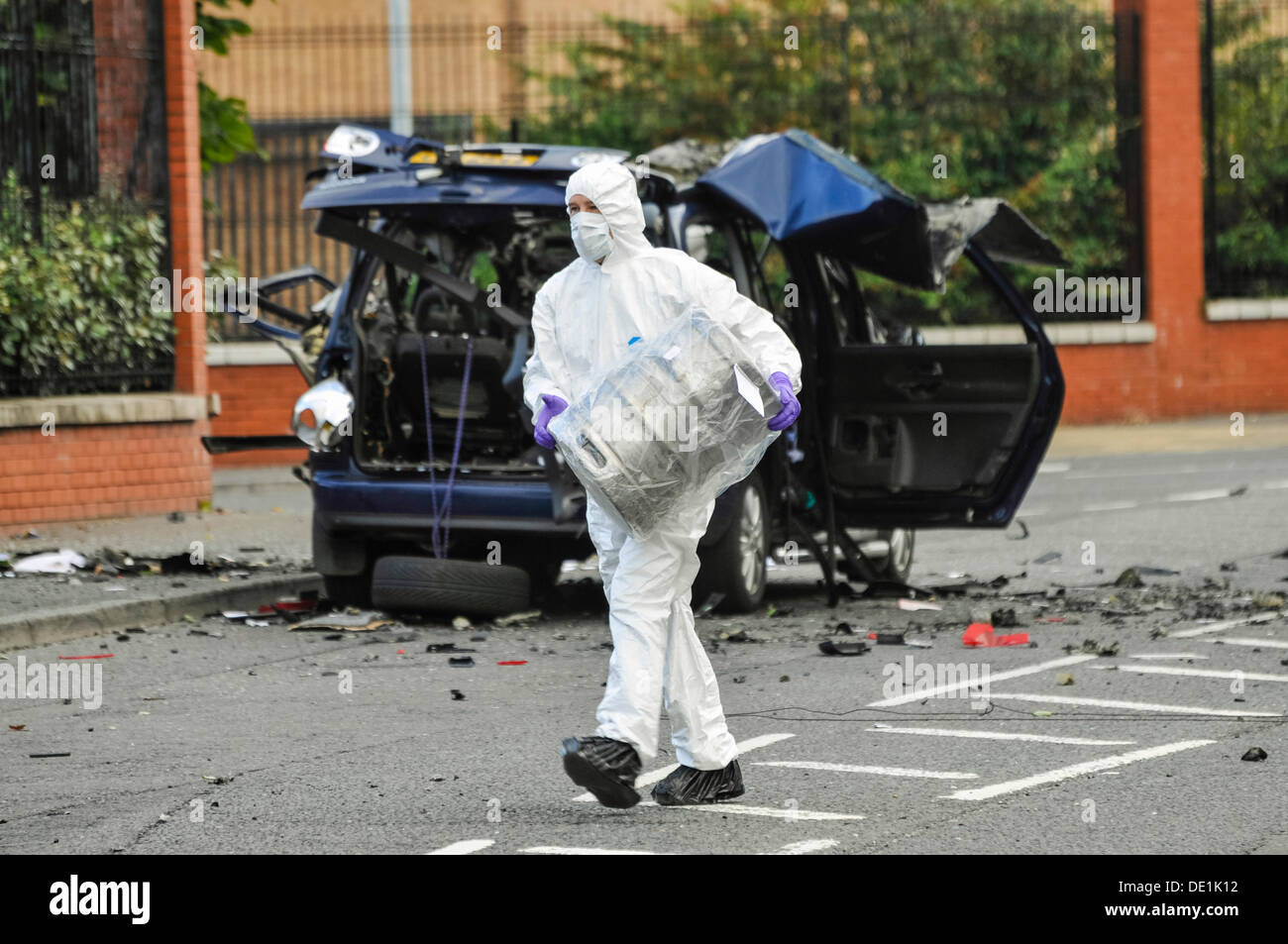 Belfast, Northern Ireland. 10th September 2013 - A PSNI forensics officer carries away the beer keg which was in the rear of an abandoned vehicle in a plastic bag.  The car was destroyed in a controlled explosion. Credit:  Stephen Barnes/Alamy Live News - Stock Image
