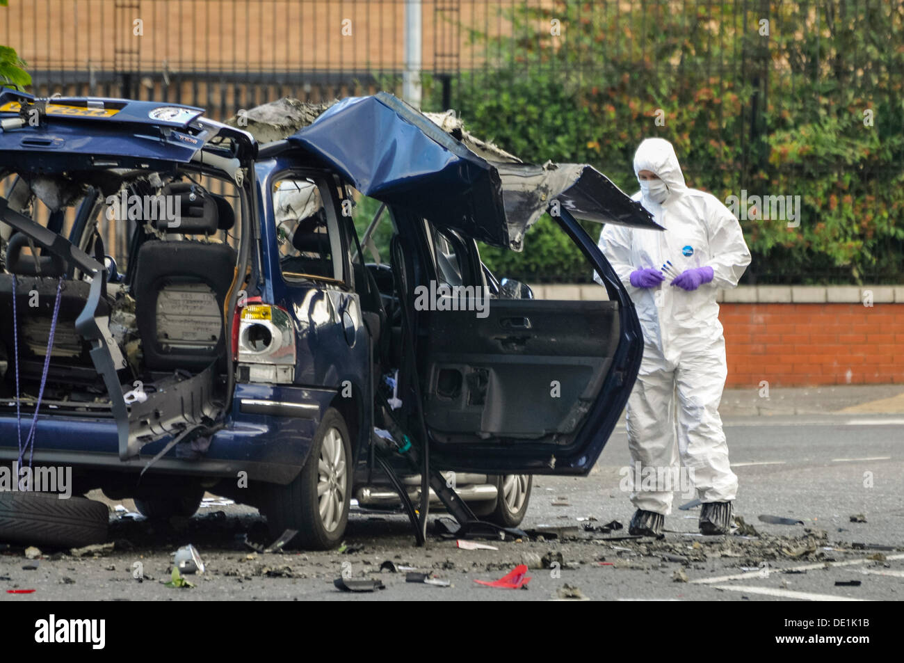 Belfast, Northern Ireland. 10th September 2013 - A PSNI forensics officer examines the wreckage of a vehicle which has been destroyed by a bomb. Credit:  Stephen Barnes/Alamy Live News - Stock Image