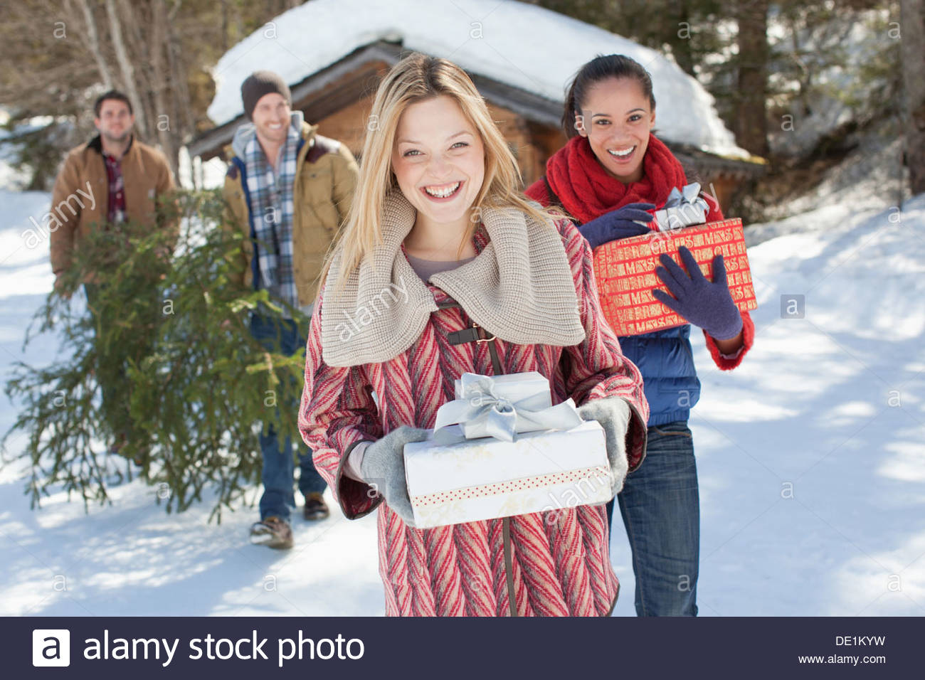 Portrait of smiling couples with fresh cut Christmas tree and gifts in snow - Stock Image
