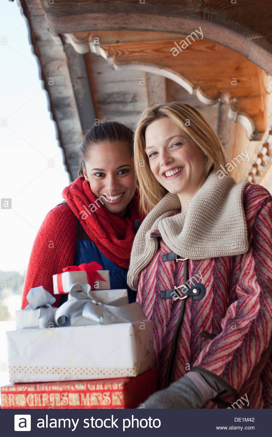 Two women with gifts outside cabin - Stock Image