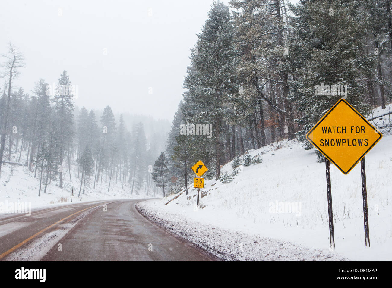 A snowy mountain road with warning signs in Cloudcroft, New Mexico, USA - Stock Image