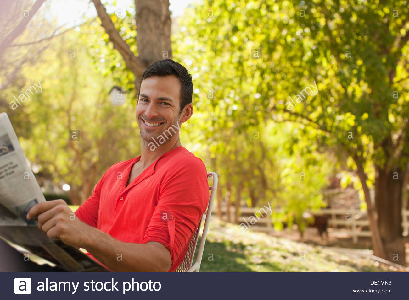 Man reading newspaper outdoors - Stock Image