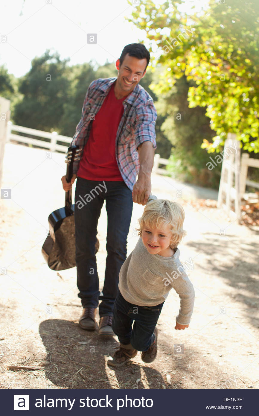 Father and son walking on dirt road - Stock Image