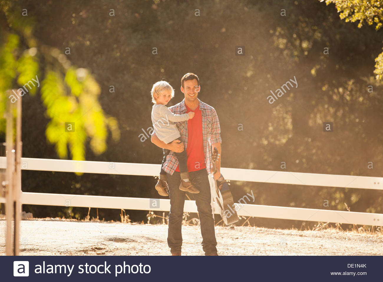 Father carrying son and guitar outdoors - Stock Image