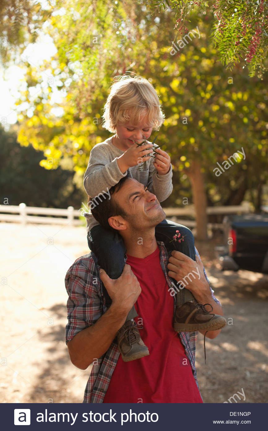 Father carrying son on shoulders - Stock Image