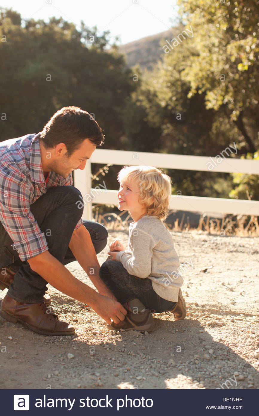 Father tying sonÂ's shoelaces - Stock Image