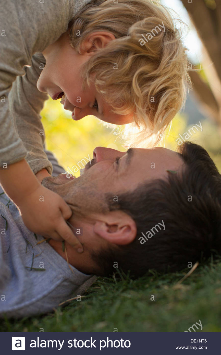 Father and son playing in grass - Stock Image