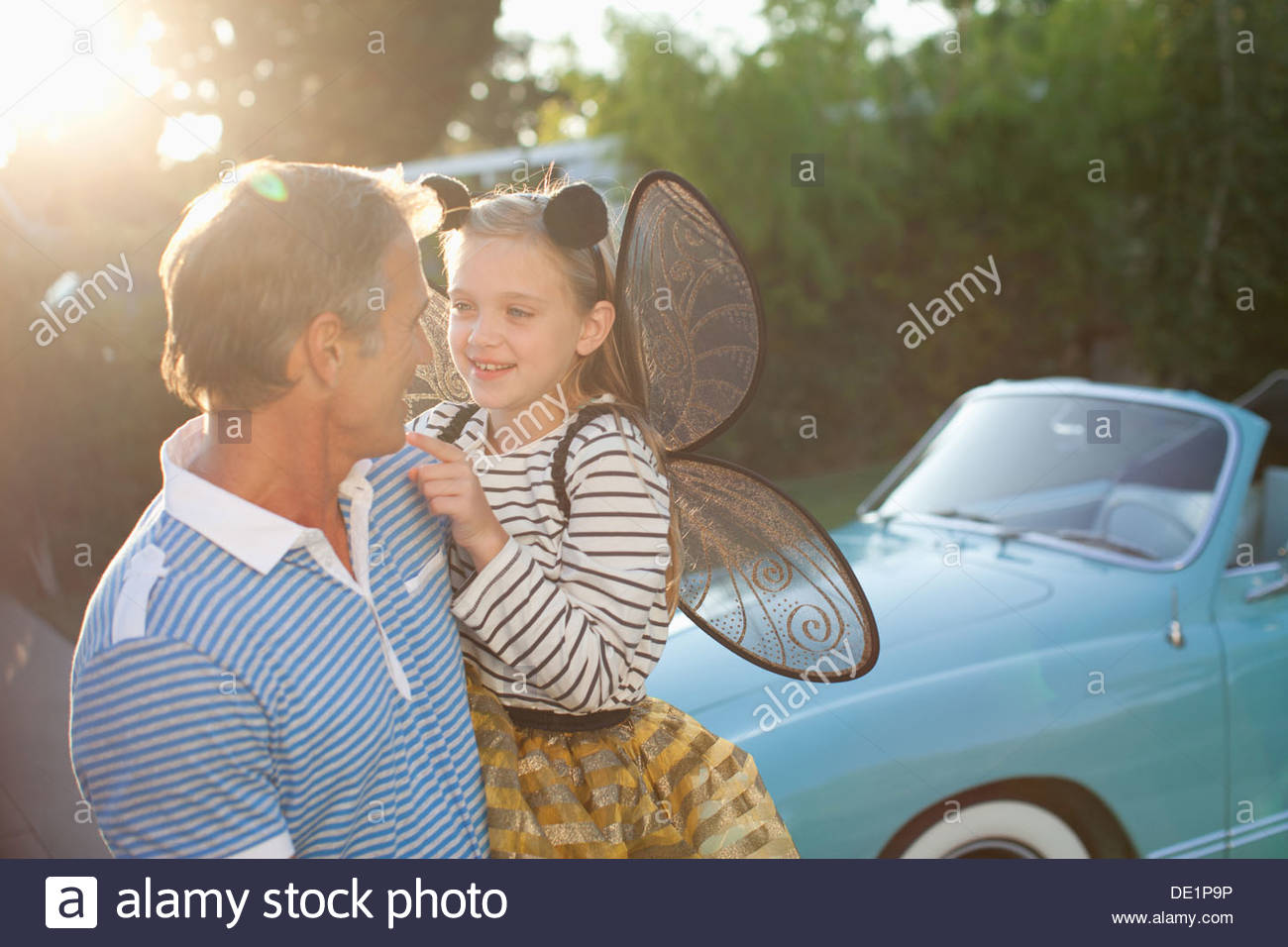 Father holding daughter in fairy wings - Stock Image
