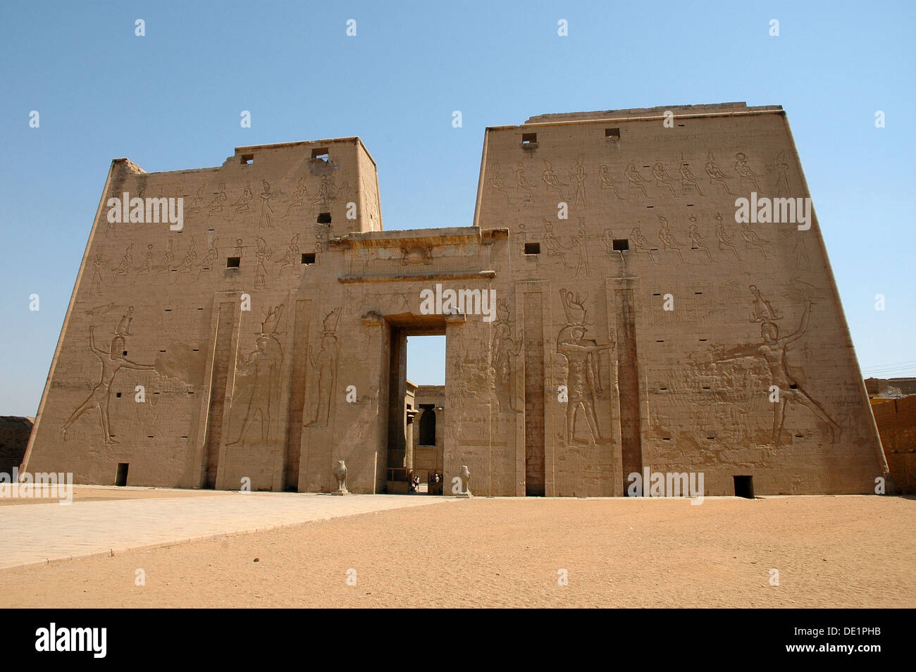 The Pylon with reliefs of the Pharaoh Ptolemy XII (Avletes) smitting his enemies in the presence of Horus the Elder. - Stock Image