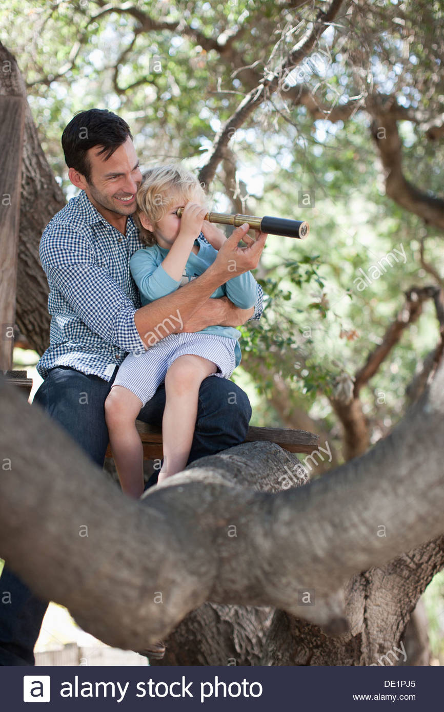 Father and son playing with telescope in tree - Stock Image
