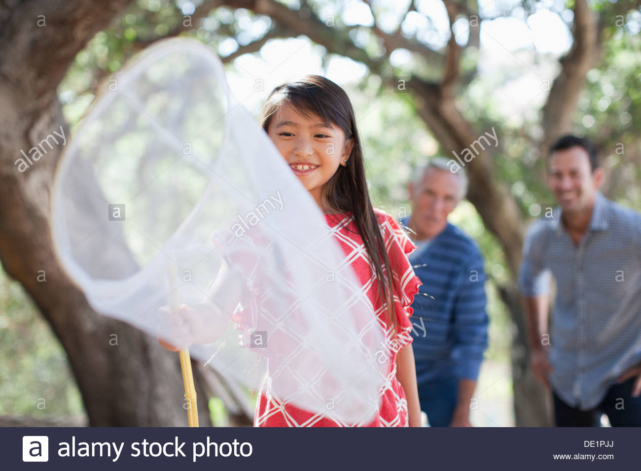 Smiling girl playing with butterfly net - Stock Image