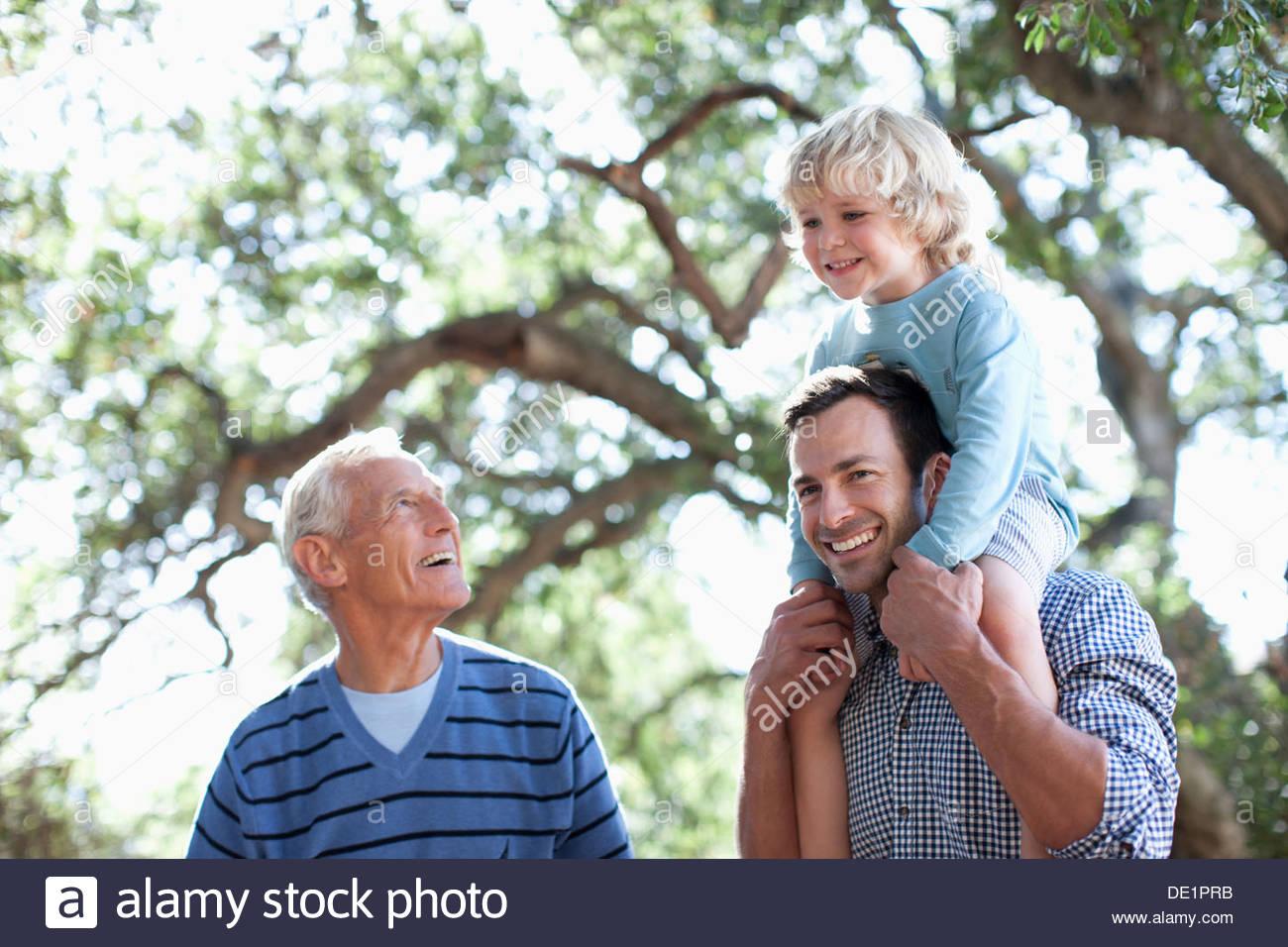 Three generations of men walking outdoors - Stock Image