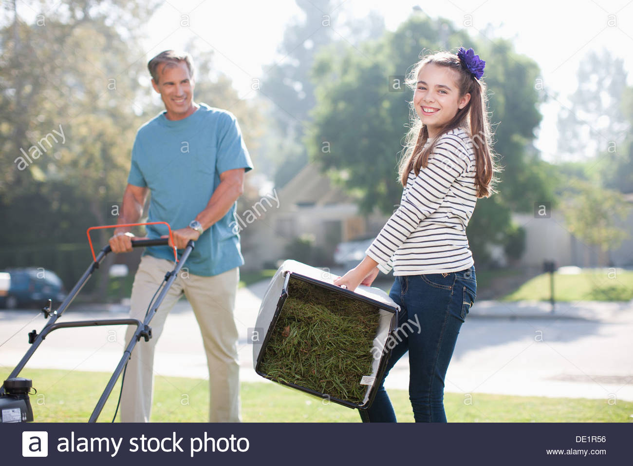 Father and daughter mowing lawn together - Stock Image