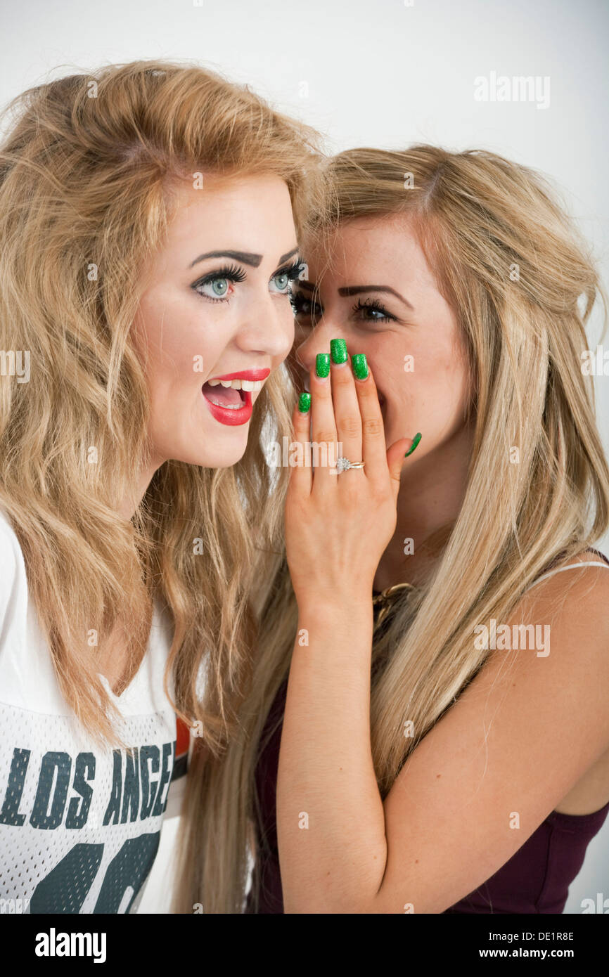 Two sixteen year old girls gossiping. - Stock Image