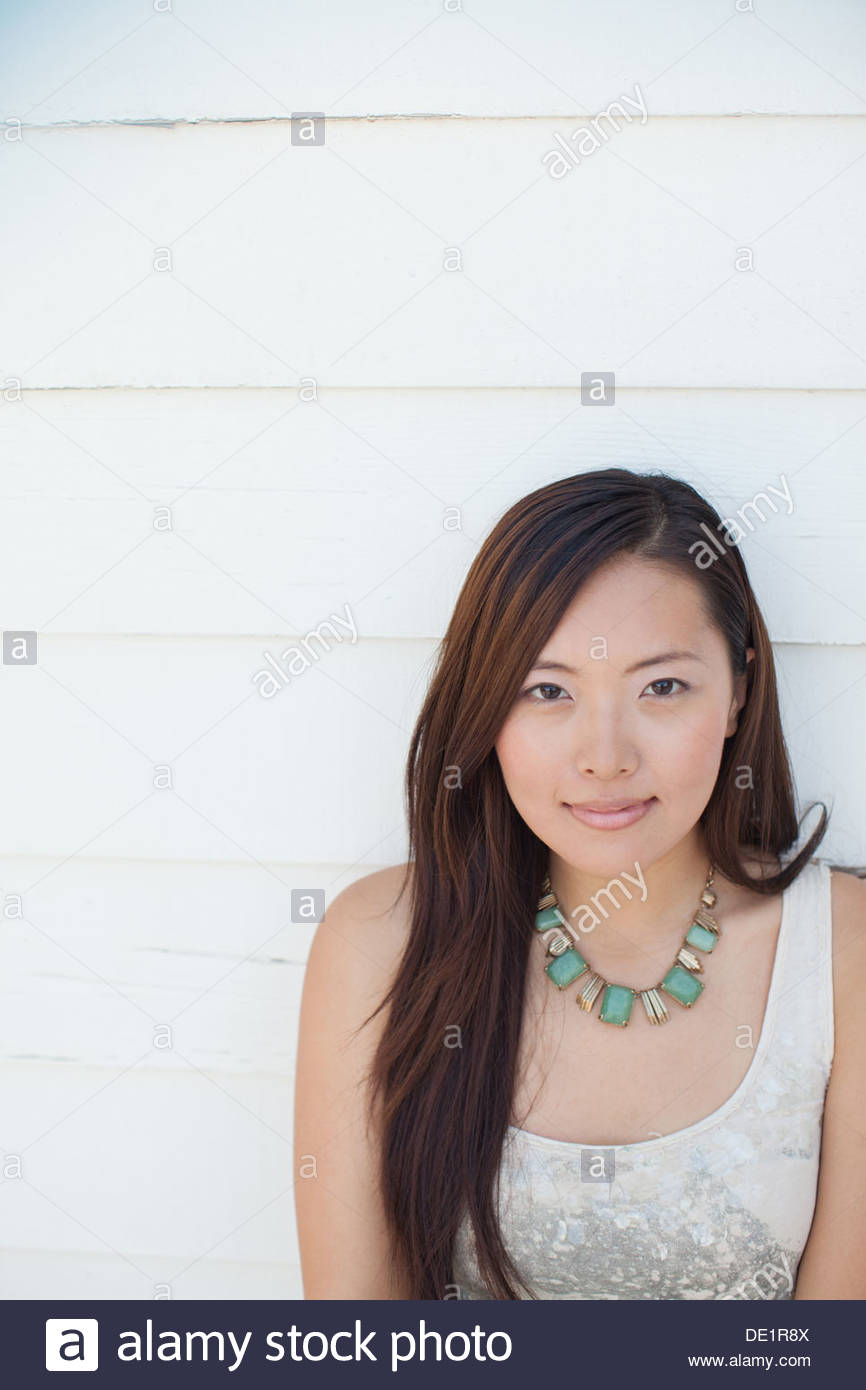 Smiling woman leaning against wall - Stock Image