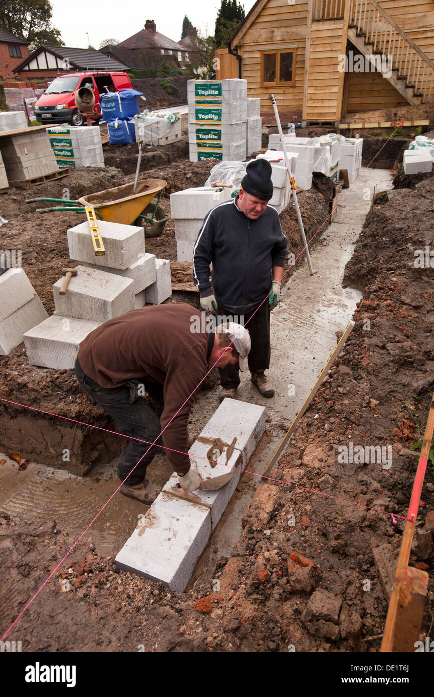 Self building house builders laying first trench blocks for Builders first