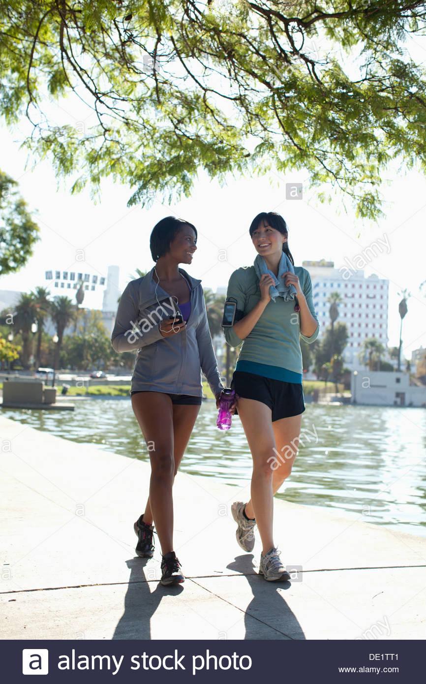 Women walking along lake in park - Stock Image