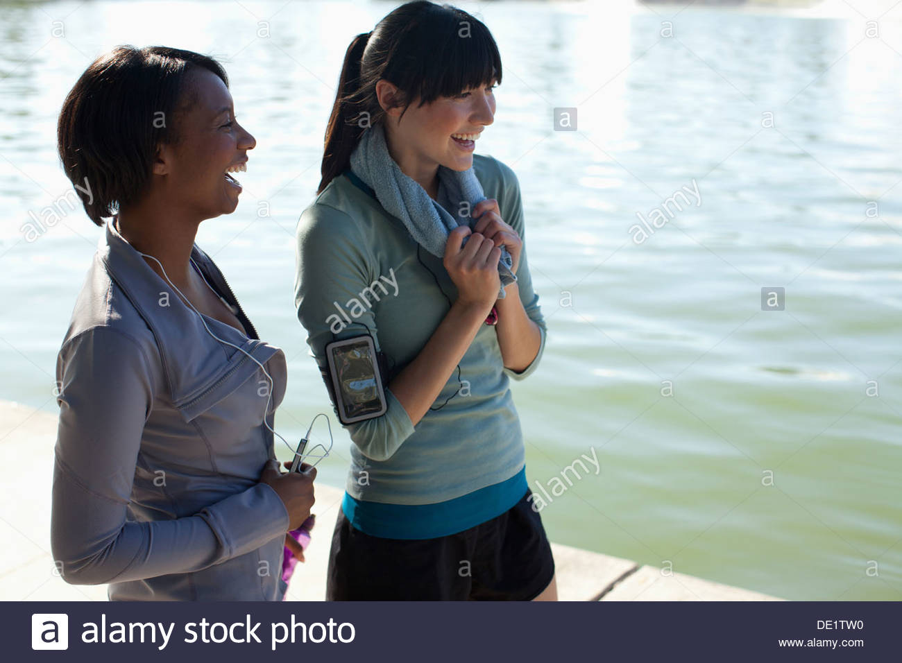 Women walking together by lake in park - Stock Image