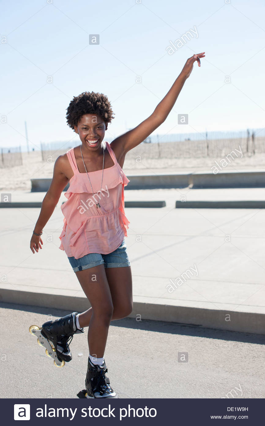 Smiling woman skating in park - Stock Image