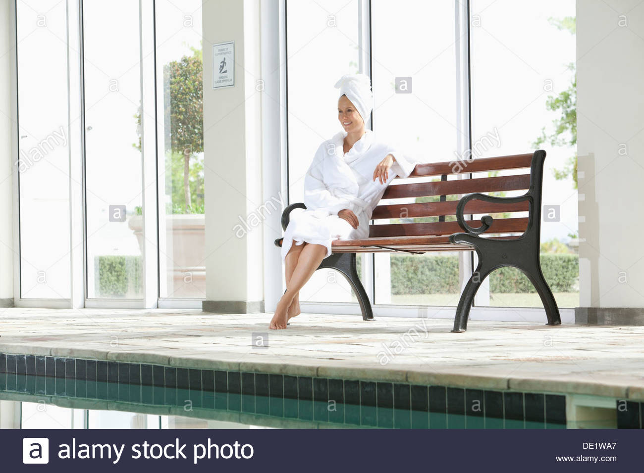 Portrait of smiling woman in bathrobe sitting on bench poolside at spa - Stock Image