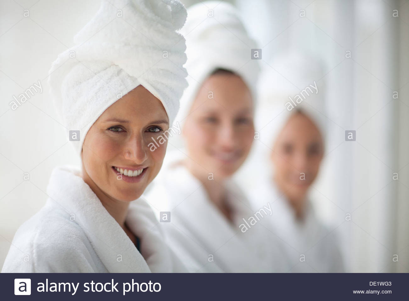 Portrait of smiling women in bathrobes and hair wrapped in towels at spa - Stock Image