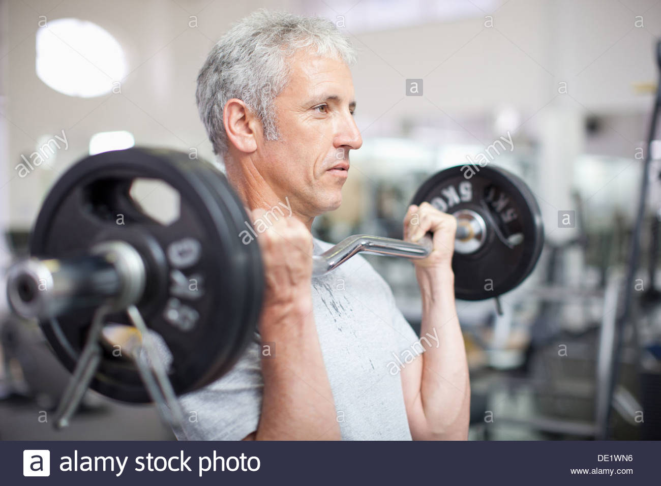 Portrait of smiling man holding barbell in gymnasium - Stock Image