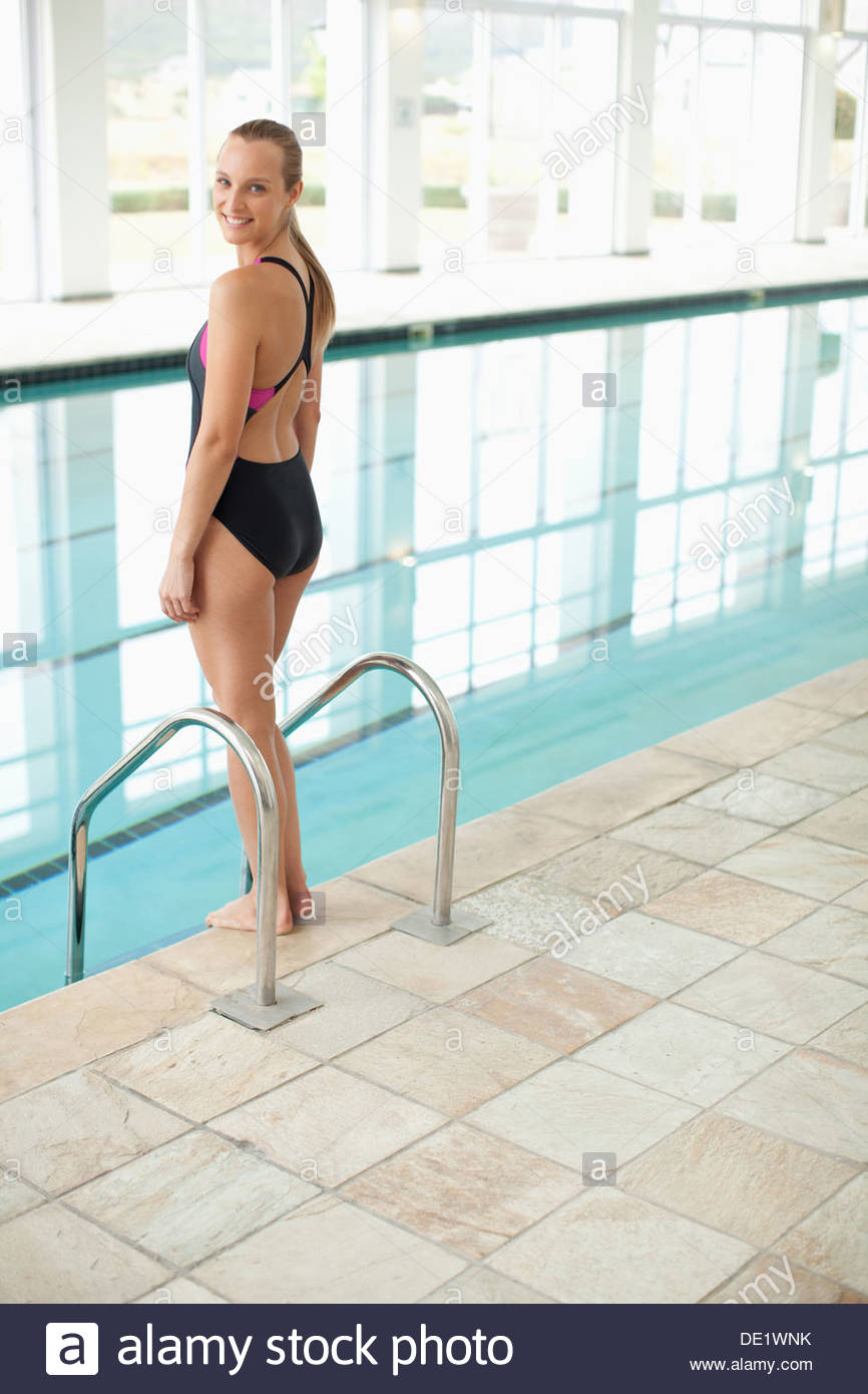 Portrait of smiling woman standing at edge of swimming pool - Stock Image