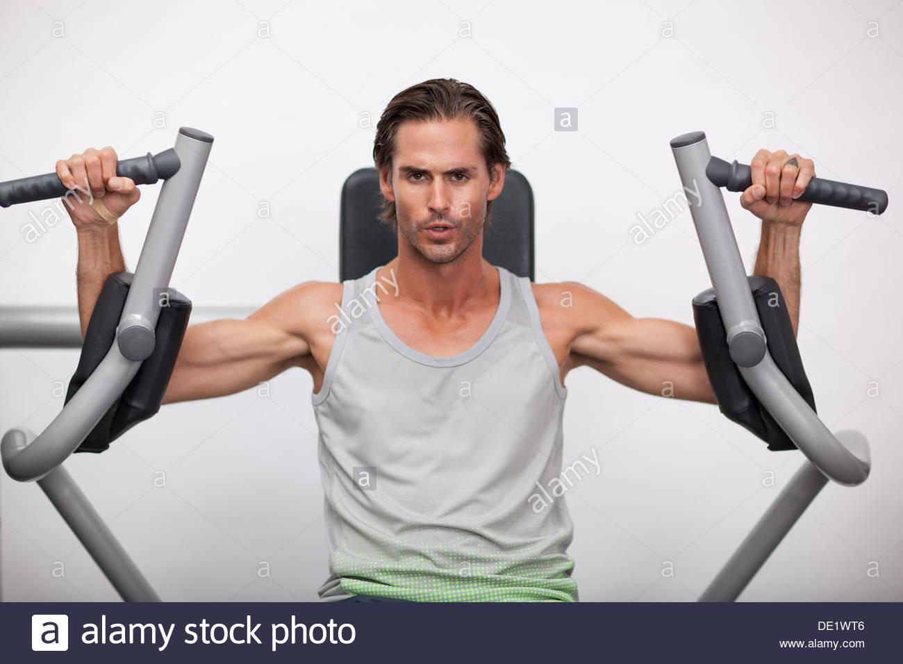 Portrait of man using exercise equipment in gymnasium - Stock Image