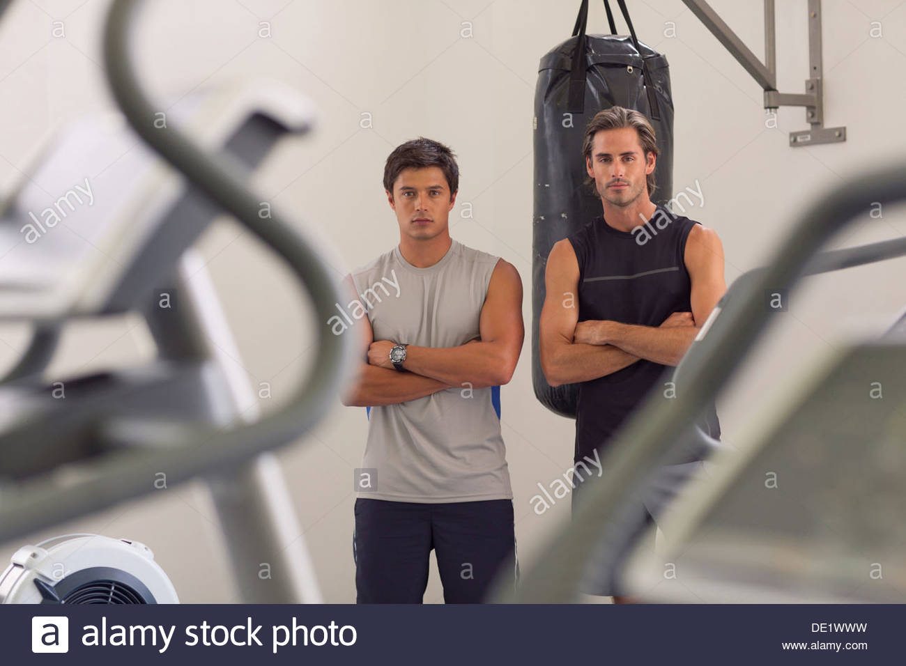 Portrait of smiling men with arms crossed in front of punching bag - Stock Image
