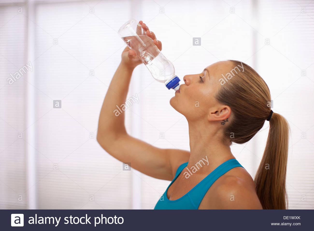 Woman in sports bra drinking water - Stock Image