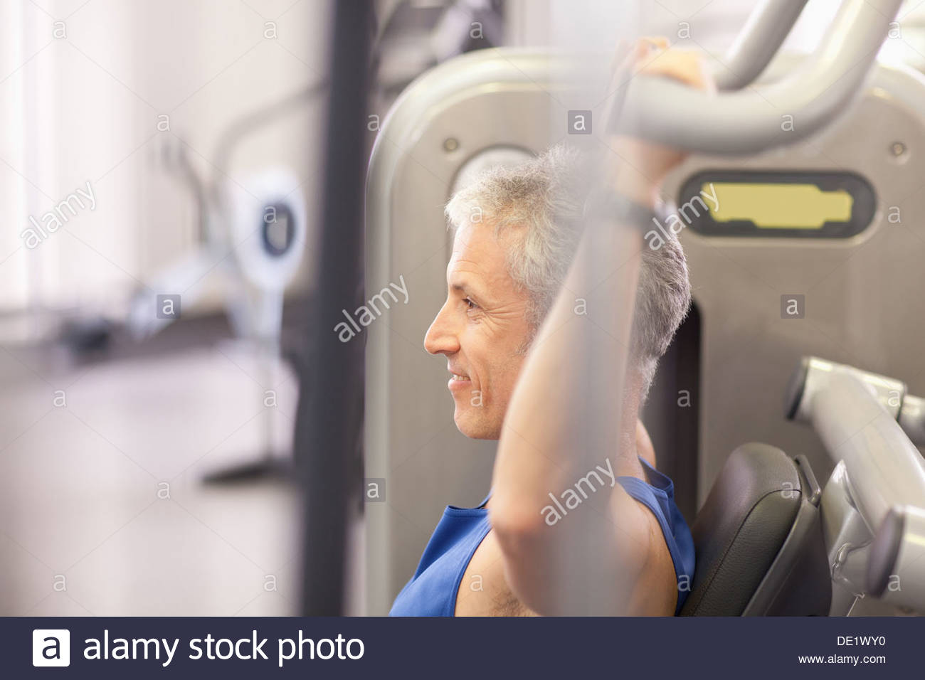 Portrait of smiling man using exercise machine in gymnasium - Stock Image