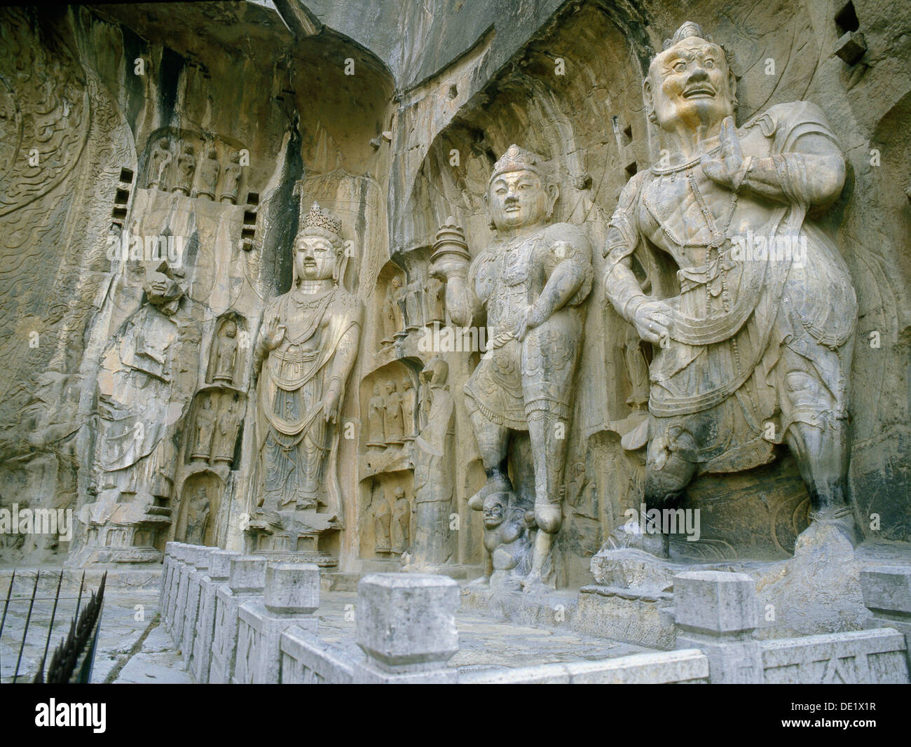 The guardian kings of Buddhism carved on the north wall of the Fengxian temple at the Longmen cave-temple complex. - Stock Image