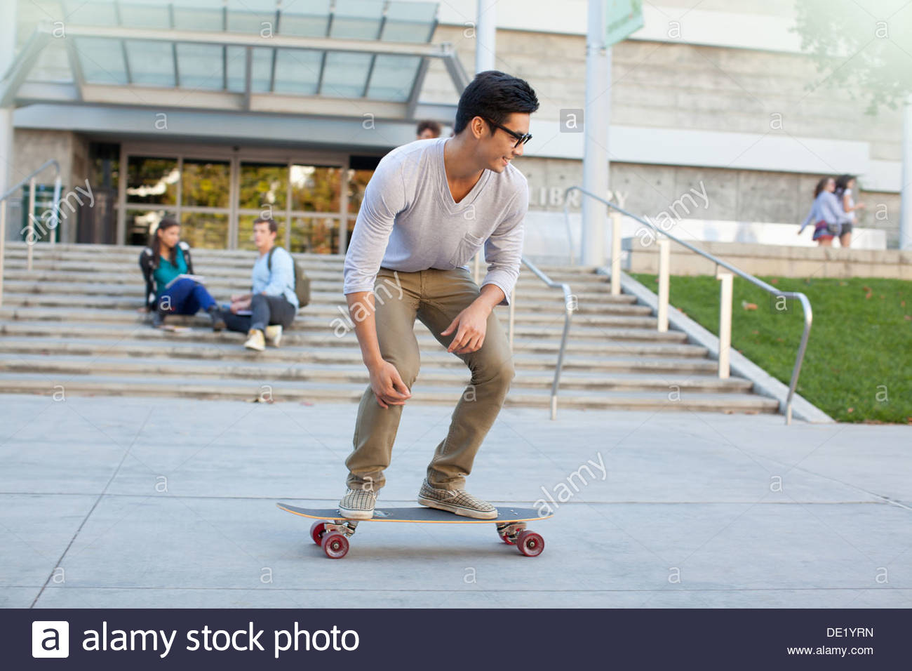 Student skateboarding on campus - Stock Image