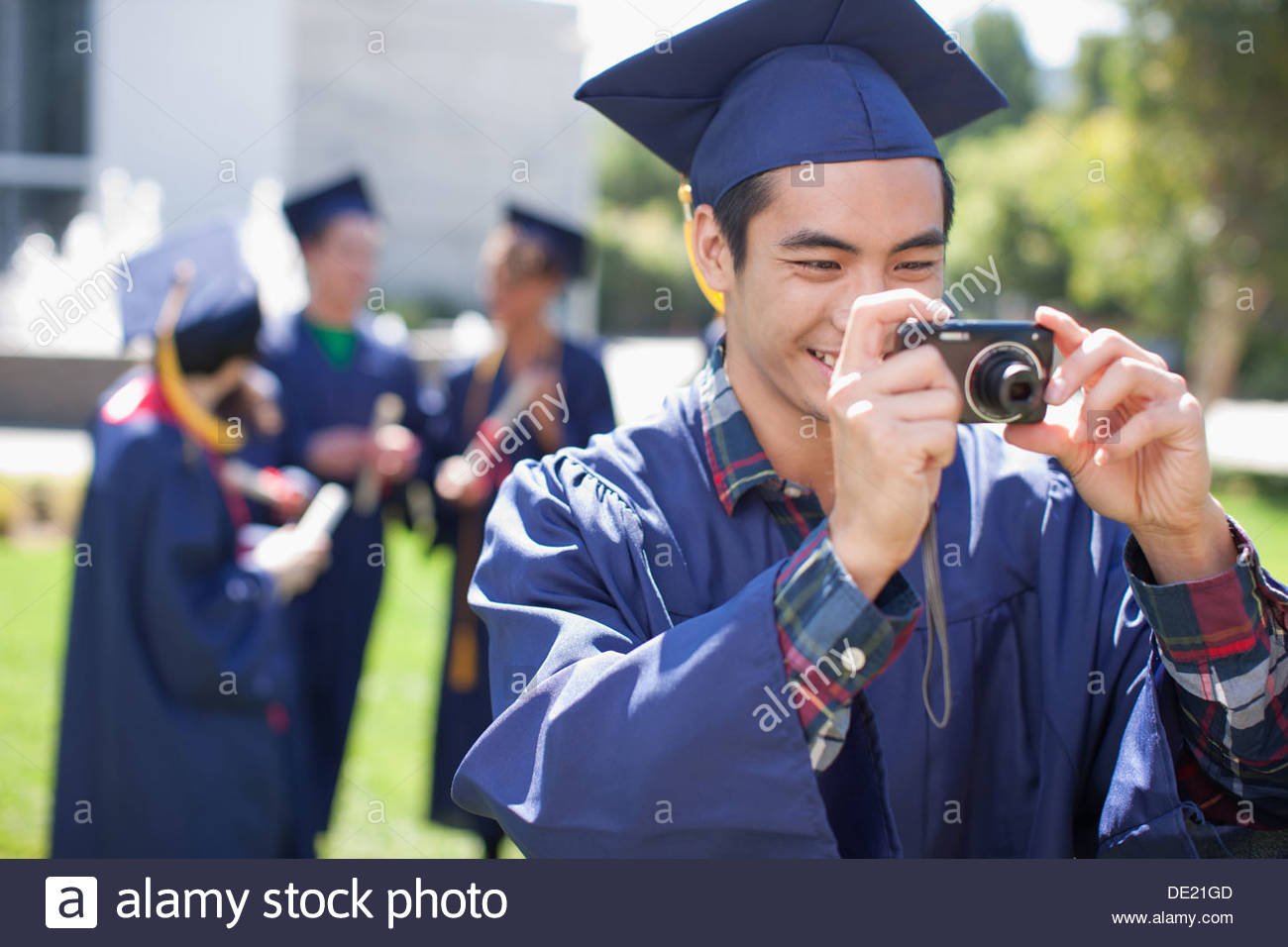 Graduate taking photograph - Stock Image
