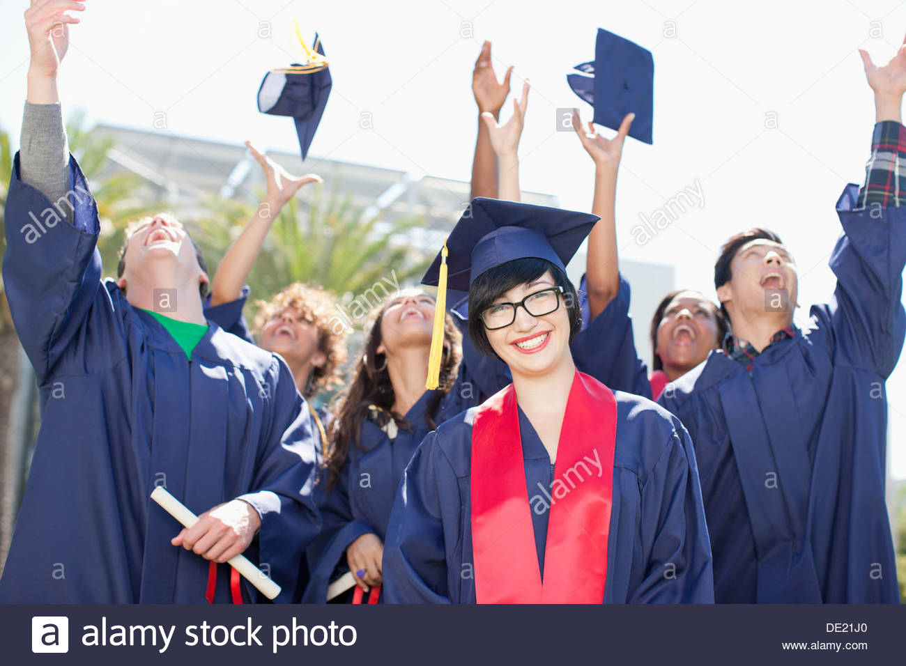 Graduates tossing caps into the air - Stock Image