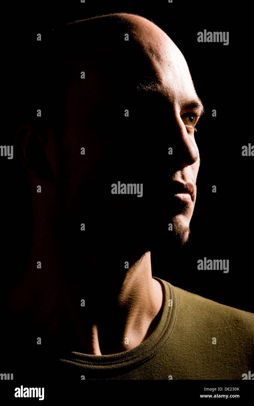 Young man in hard side light, portrait - Stock Image