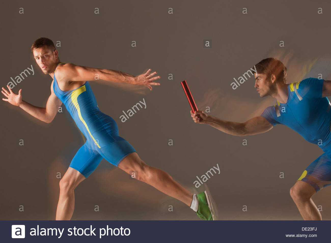 Blurred view of athletes passing baton - Stock Image