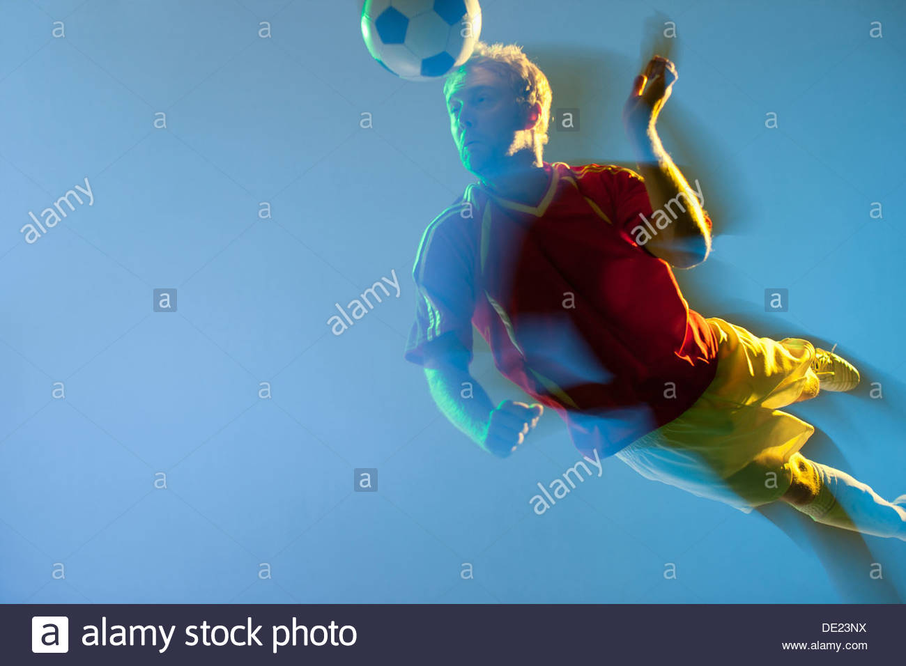 Blurred view of soccer player heading ball - Stock Image