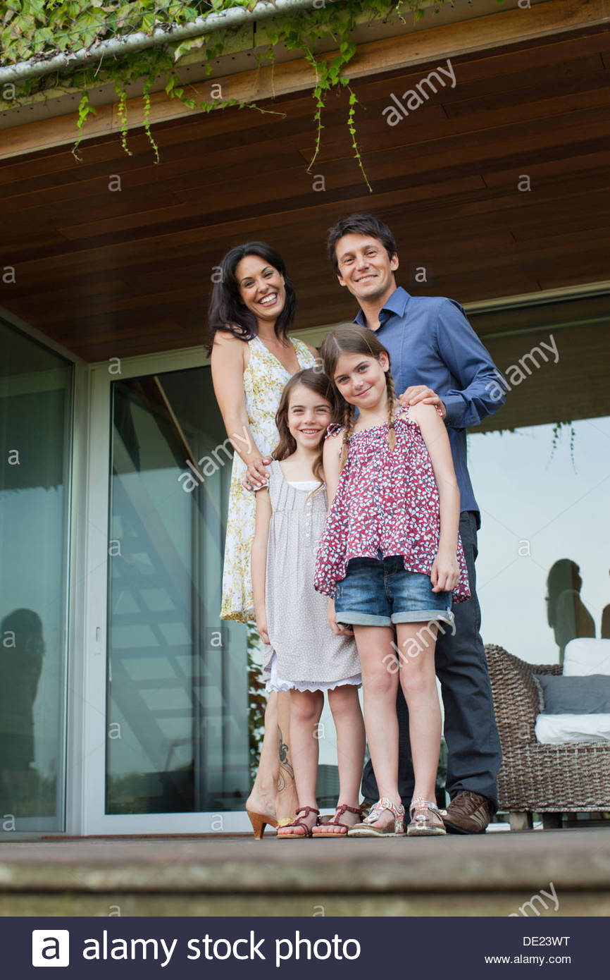 Family standing together on patio - Stock Image
