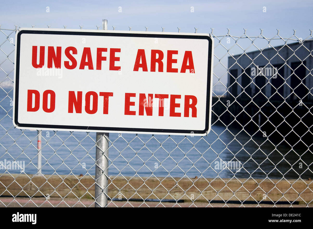 ´Unsafe Area Do Not Enter´. Sign on chain link fence. San Francisco. California. USA. - Stock Image