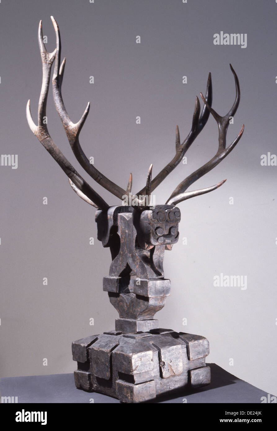 Wooden sculpture of mythical being with deer antlers. - Stock Image