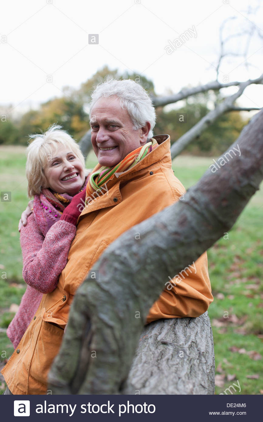 Senior couple hugging outdoors in autumn - Stock Image