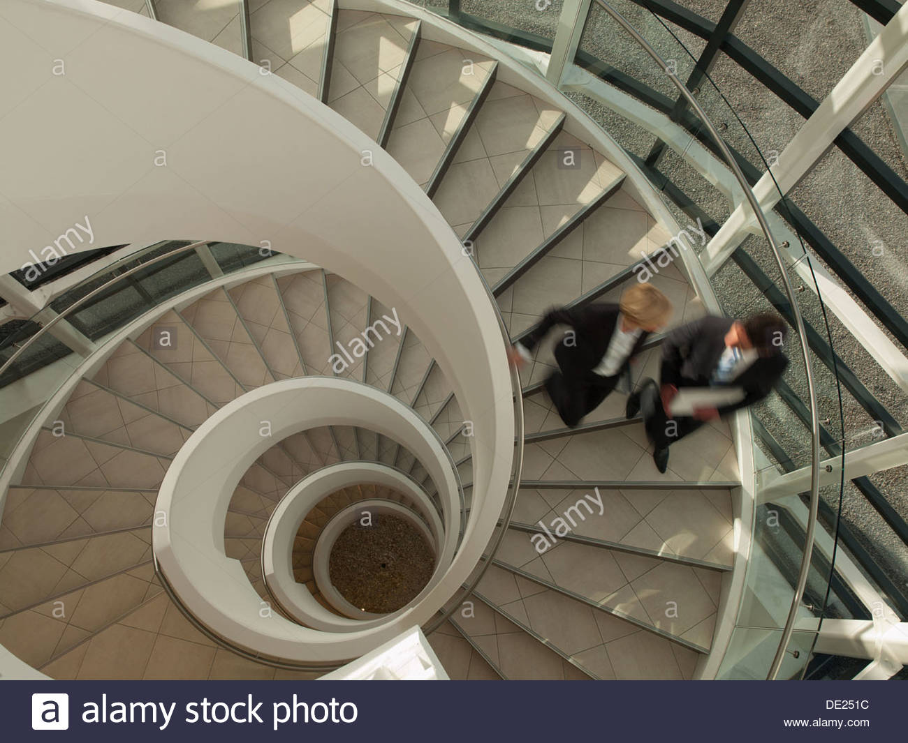 Business people descending circular staircase - Stock Image