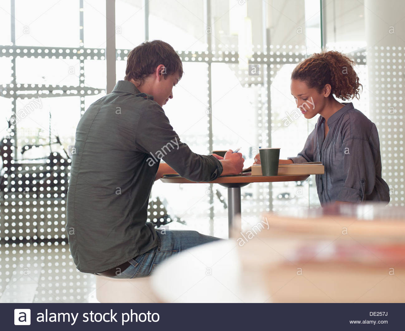 Smiling couple sitting at table in college cafeteria - Stock Image