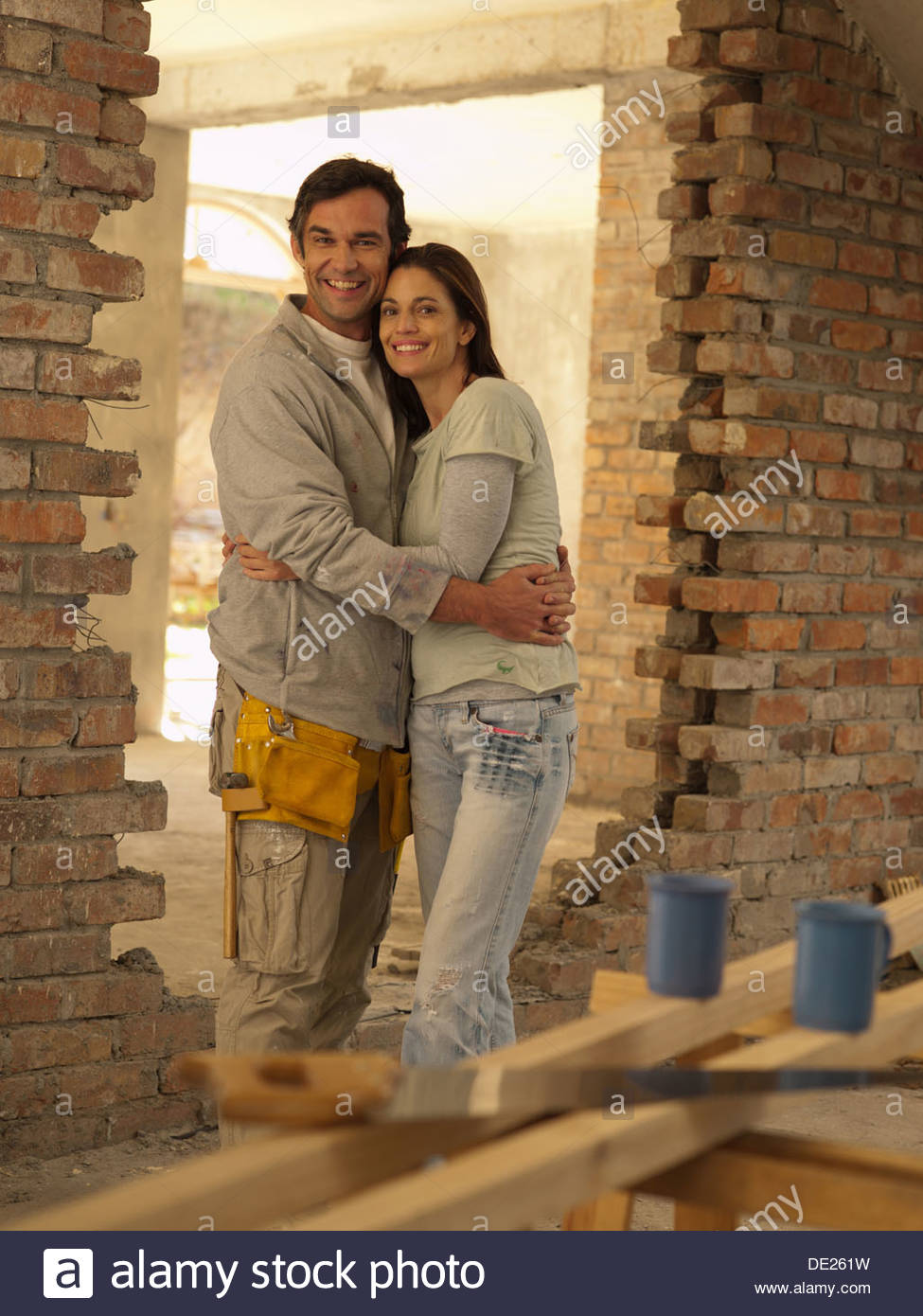 Couple hugging in doorway of house under construction - Stock Image