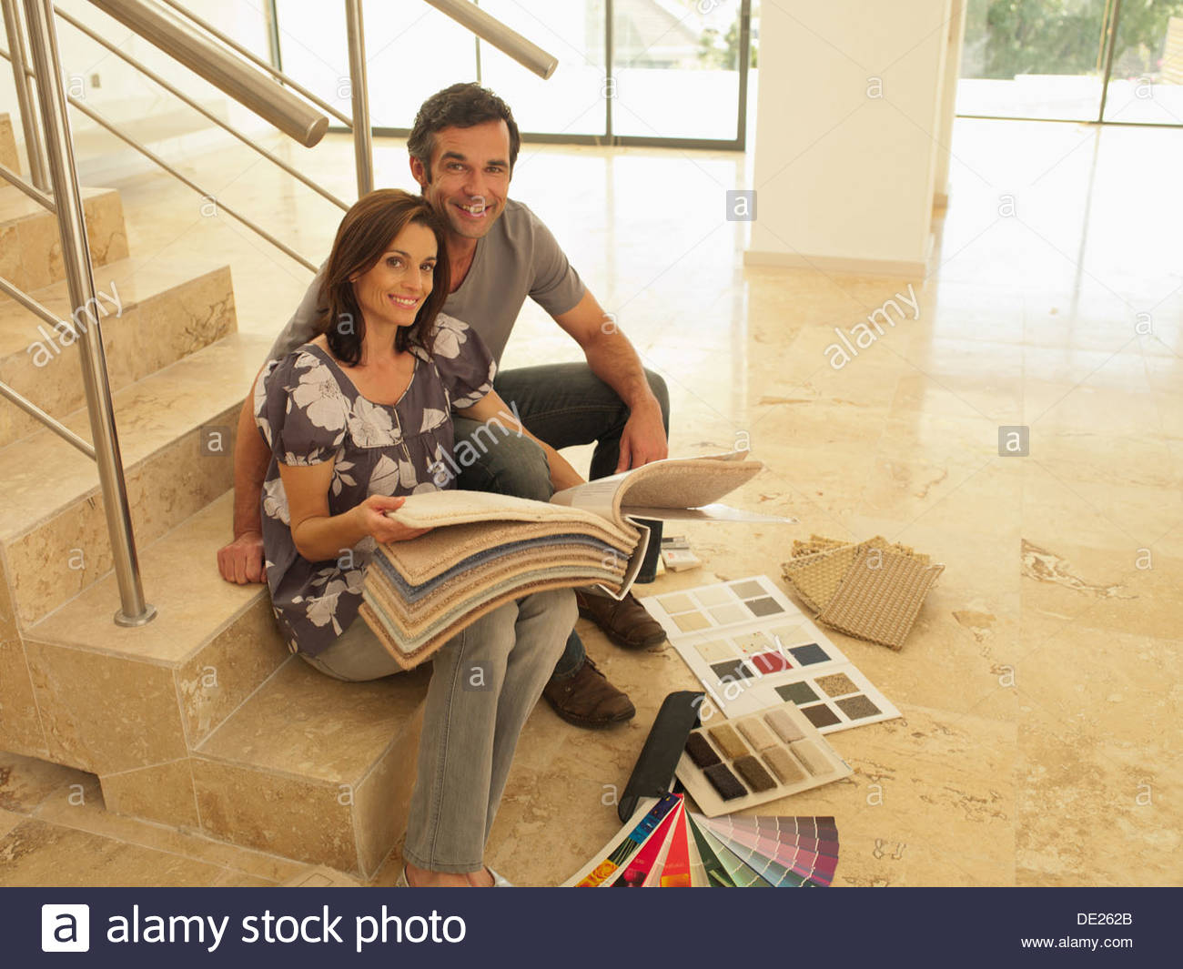 Couple looking at carpet samples in empty house Stock Photo