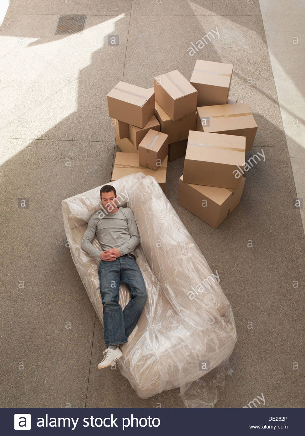 Man sleeping on sofa wrapped in plastic - Stock Image