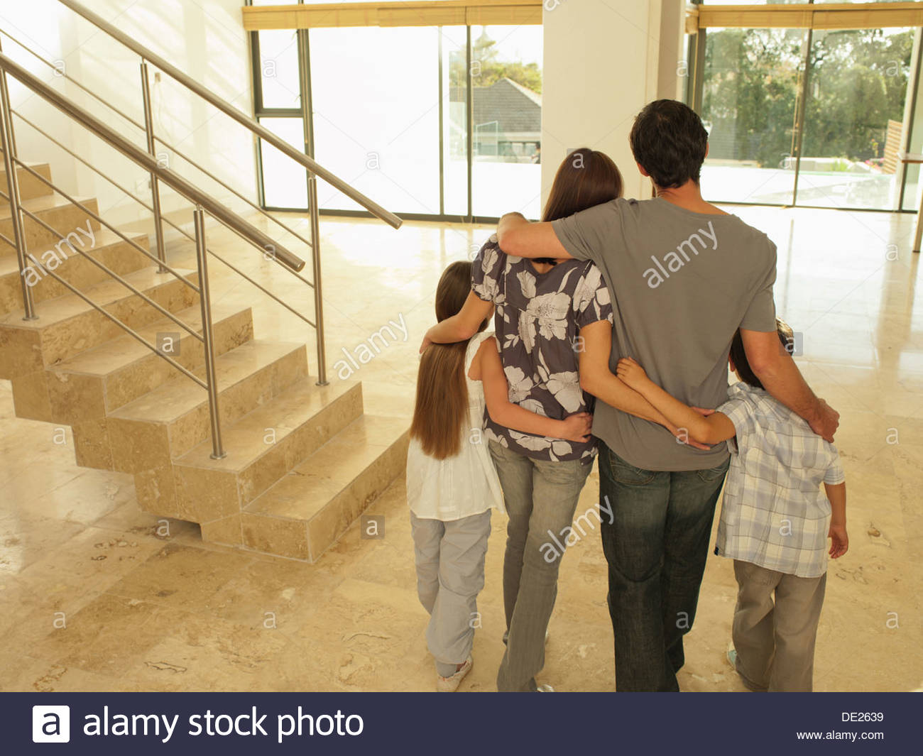 Family hugging in new house - Stock Image