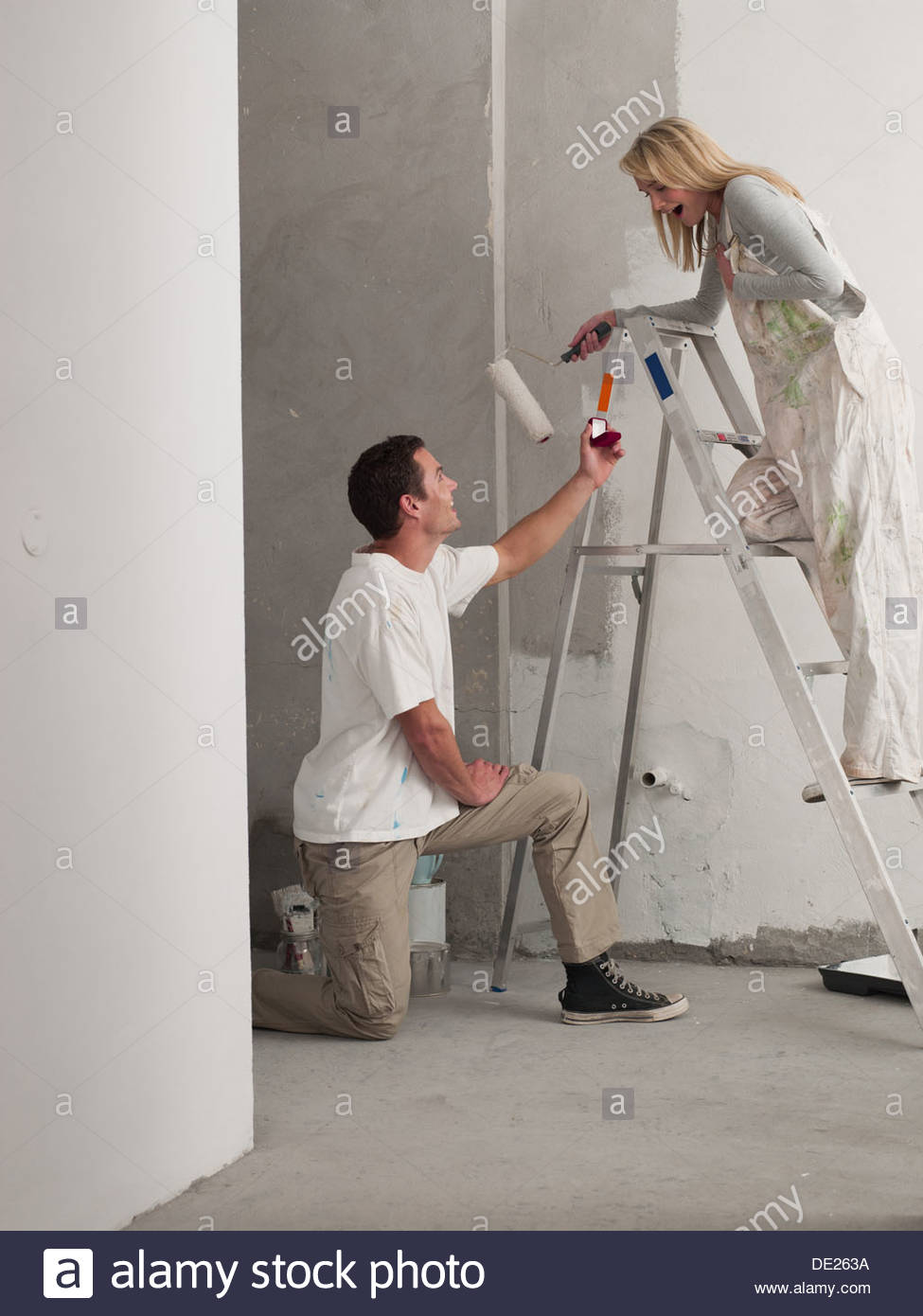 Man proposing to woman painting wall - Stock Image