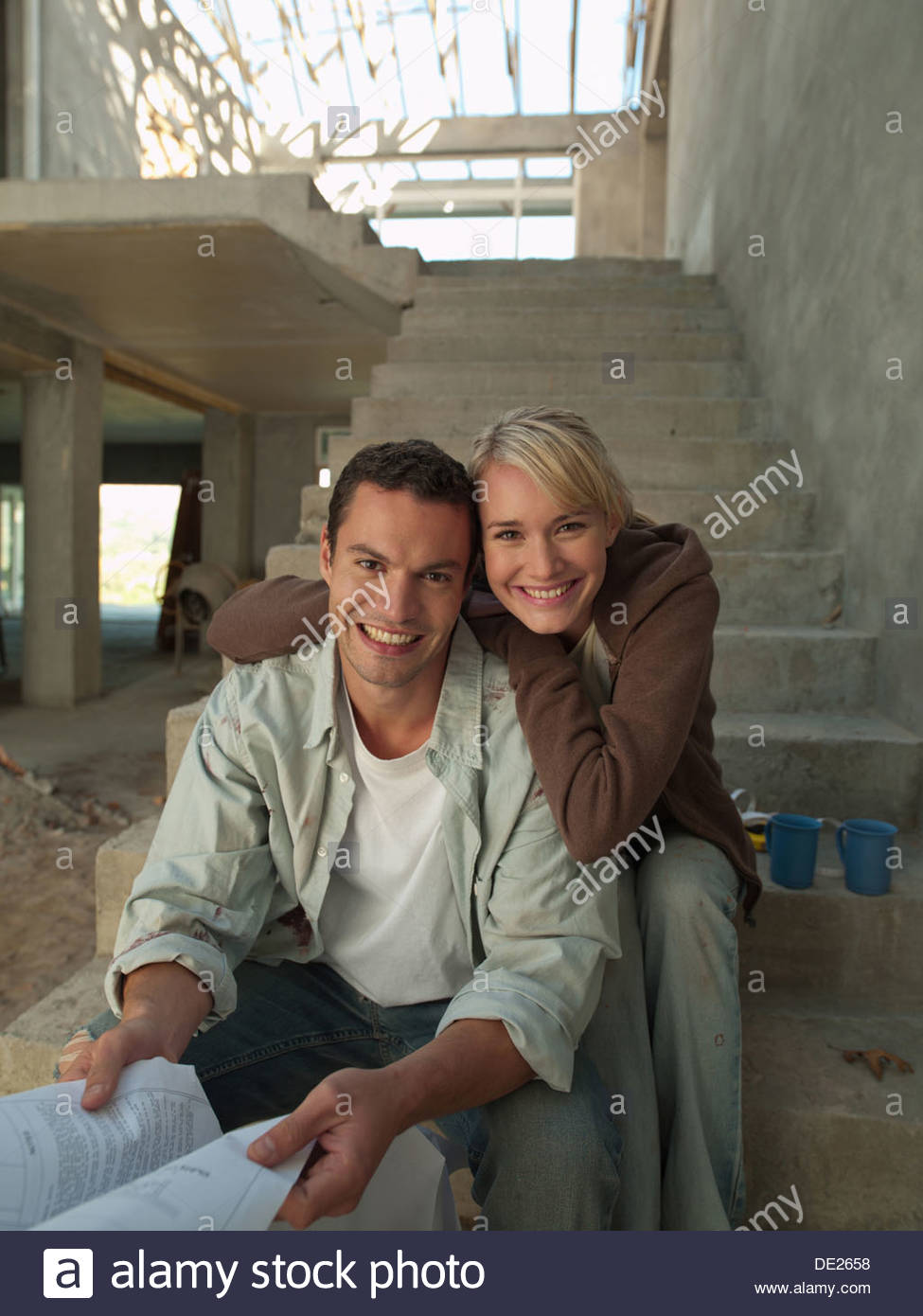 Couple looking at blueprints on staircase of house under construction - Stock Image